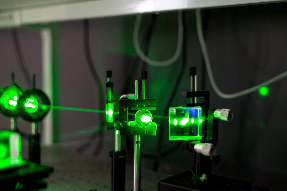 A green laser shines through several pieces of glass